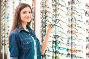 Young woman at optician with glasses is looking for sunglasses- Complete Family Eye Care- Corpus Christi Moms Blog