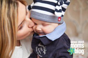 should-i-stay-or-go-to-work-mom-kissing-baby-corpus-christi-moms-blog