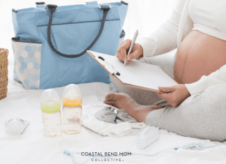Image of an expecting mom, sitting cross legged on a white bed, making a list on a clipboard, planning things to take to the hospital. Also pictured: a blue diaper bag, 2 baby bottles, and a pacifier.