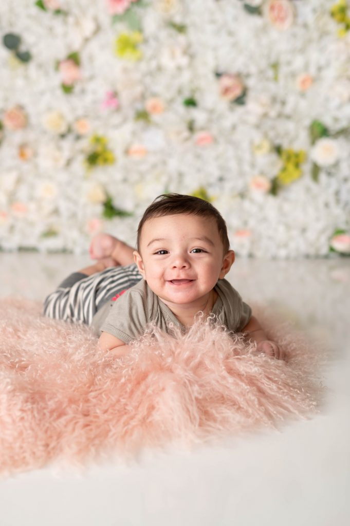 Baby Wesley laying on a pink fluffy rug in front of a floral wall.
