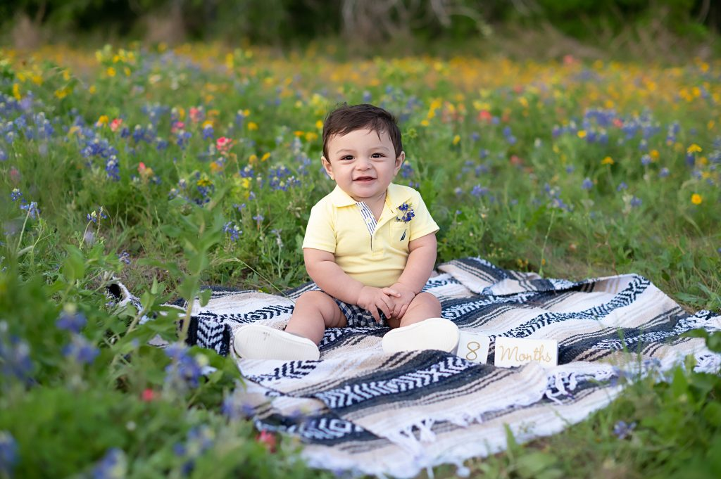 Image of baby Wesley, wearing a yellow polo shirt, sitting on a blue and white blanket, in a field of wildflowers. The baby is smiling.