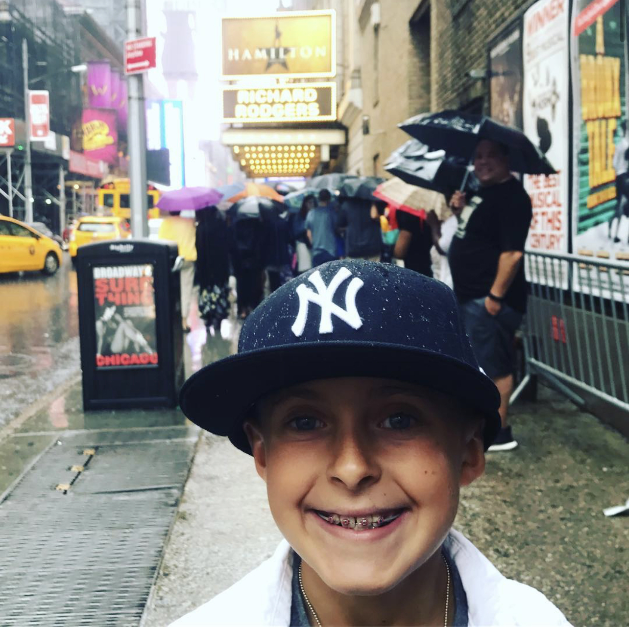 Image of a boy, standing on the street in New York City. Marquis at the Richard Rogers Theatre on Broadway in the background. Marquis is advertising HAMILTON the musical. The boy is grinning from ear to ear, wearing a New York Yankess baseball cap. The boy has braces on his teeth.