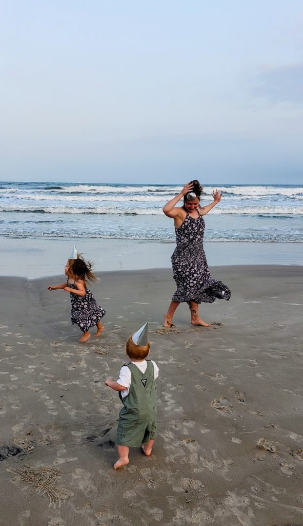 Mom and two kids dancing on the beach